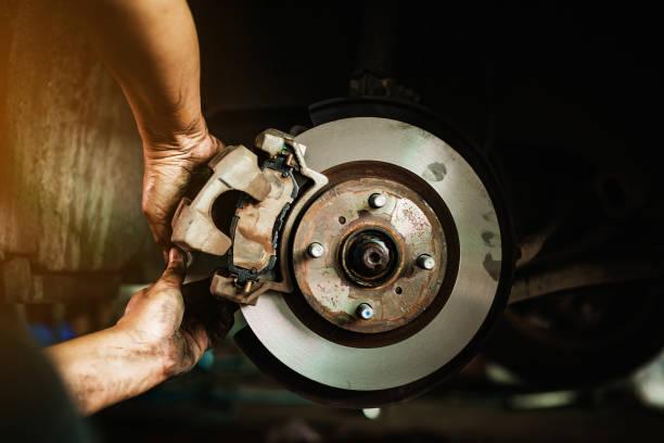 selektive fokusscheibenbremse am auto, im prozess des neuen reifenaustauschs, autobremsenreparatur in der garage - bremse stock-fotos und bilder