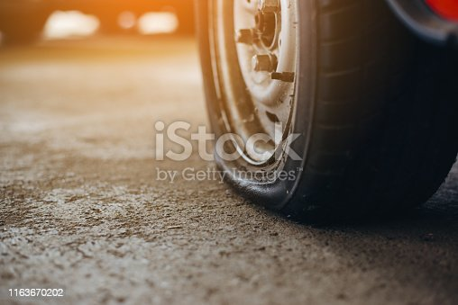 istock Selective focus flat tire of old car park on the street waiting for repair,copy space, (vintage tone) 1163670202