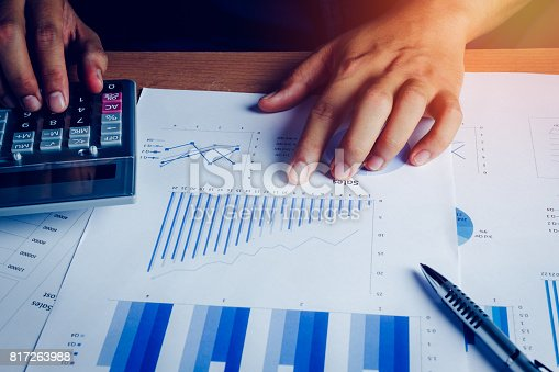 istock Selective focus hand asian business man is calculating finance and accounting with growth up paper chart on wood table in home office.Pen calculator graph document on desk.economy,saving,financial. 817263988