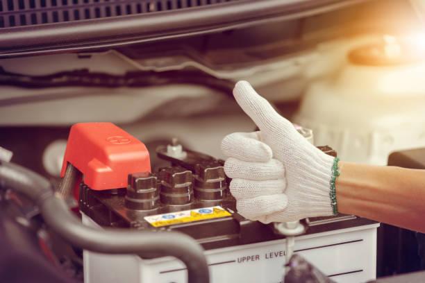 tiefenschärfe, mann hand überprüfen autobatterie auf auto-motor-system - batterie stock-fotos und bilder