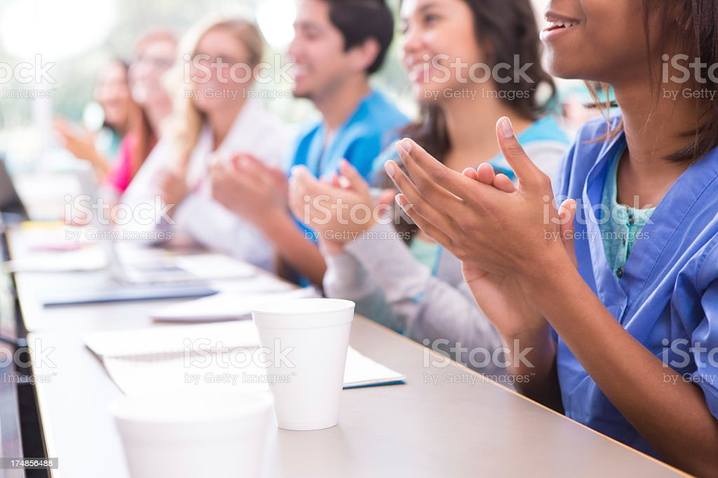 Selective focus, medical or nursing students applauding college professor royalty-free stock photo