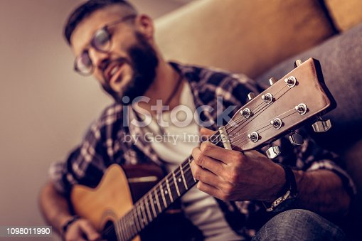 istock Selective focus of a guitar in male hands 1098011990