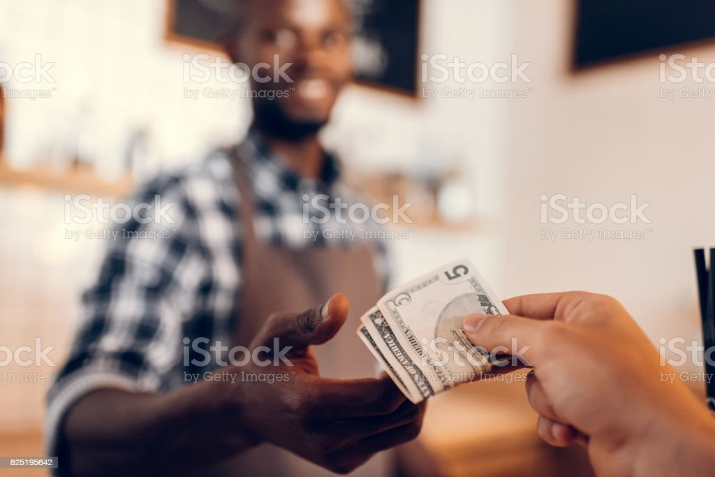 selective focus of african american barista taking cash payment on bar counter in cafe stock photo