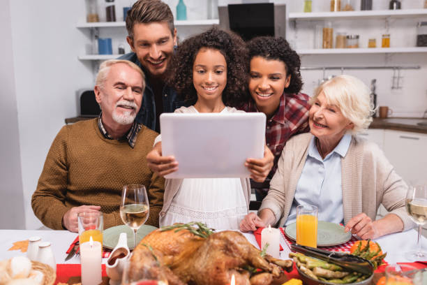 Selective focus of african american girl holding digital tablet near parents during thanksgiving celebration stock photo