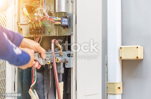 istock Selective focus of Air Conditioning Repair, repairman on the floor fixing air conditioning system 1175145959