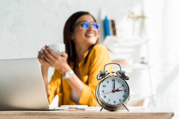 selective focus of alarm clock and happy freelancer having coffee break in home office with laptop stock photo