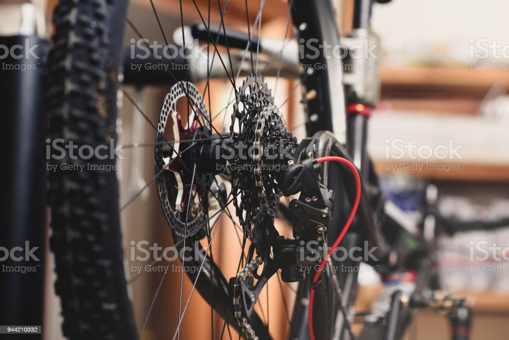selective focus of bicycle wheel with chain in workshop stock photo