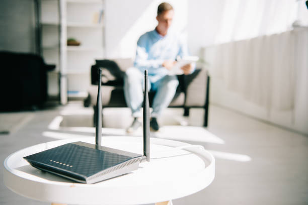 selective focus of black plugged router on white table and businessman sitting on sofa - router foto e immagini stock