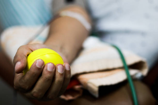 selective focus of blood collection during blood donation and ball in palm for squeezing selective focus of blood collection during blood donation and ball in palm for squeezing blood donation stock pictures, royalty-free photos & images