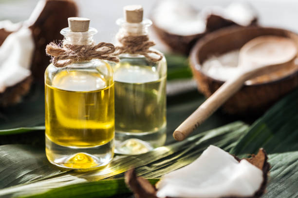 selective focus of bottles with coconut oil near cracked coconuts on green palm leaves selective focus of bottles with coconut oil near cracked coconuts on green palm leaves coconut oil stock pictures, royalty-free photos & images