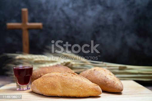 selective focus of bread and grape beverage and stand wood cross for background and inspiration