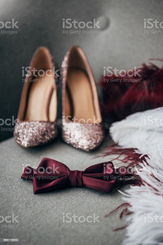 selective focus of bridal shoes, grooms bow tie and feathers for rustic wedding on armchair zbiór zdjęć royalty-free
