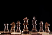 selective focus of brown wooden queen on chessboard isolated on black