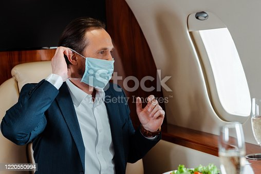 Selective focus of businessman putting on medical mask near champagne and salad on table in airplane