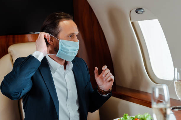 Selective focus of businessman putting on medical mask near champagne and salad on table in airplane stock photo