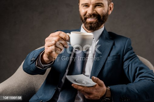1081599130 istock photo selective focus of cup with coffee with bearded businessman on background 1081599158