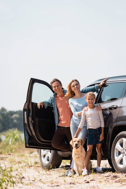 Selective focus of family with golden retriever looking at camera while standing near car outdoors stock photo