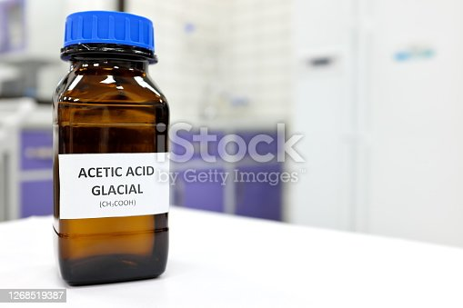Selective focus of glacial Acetic acid solution in brown amber bottle. Blur white laboratory backdrop with copy space.