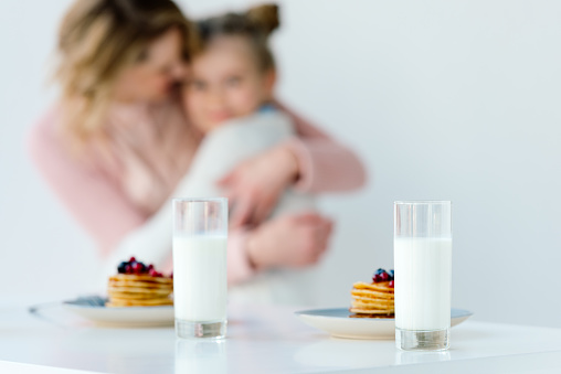 istock selective focus of glasses of milk and pancakes on tabletop with family hugging behind 957700692