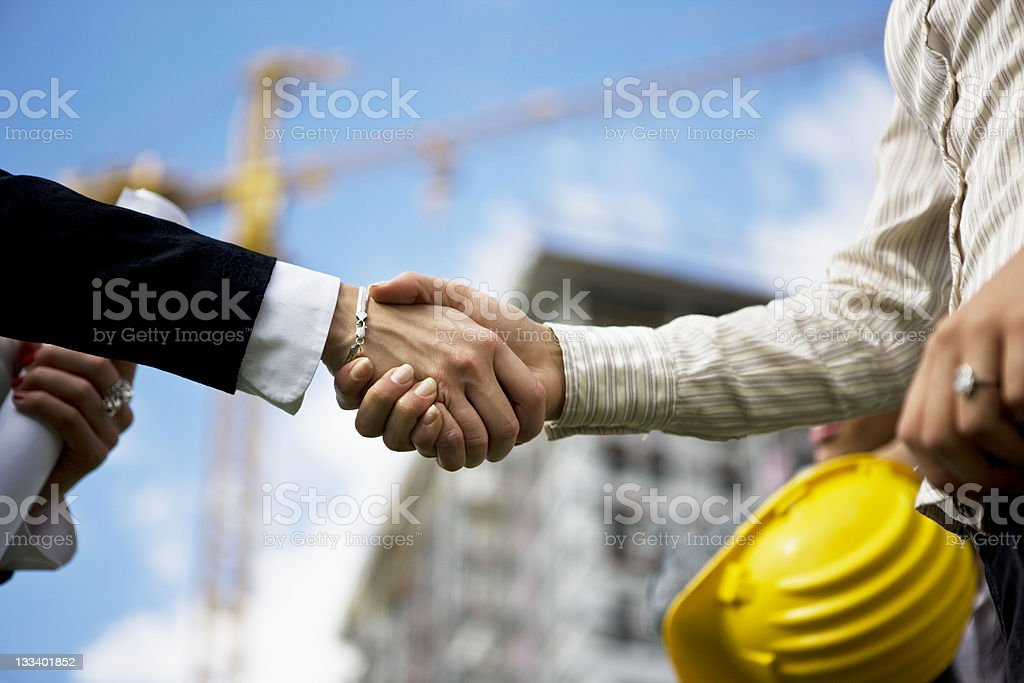 Selective focus of handshake in construction yard royalty-free stock photo