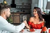 selective focus of happy couple celebrating christmas and clinking by champagne glasses at served table with candles at home
