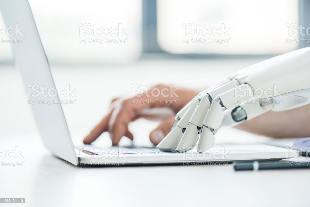 selective focus of human and robot hands typing on laptop at workplace royalty-free stock photo