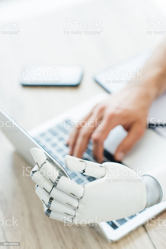 selective focus of human and robot hands using laptop at wooden table royalty-free stock photo