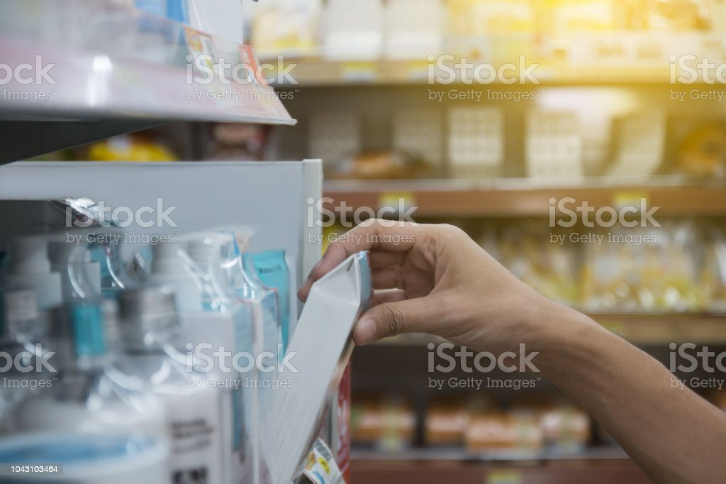 Selective focus of Human's hand get beauty products from steel shelf in store. shopping concept stock photo