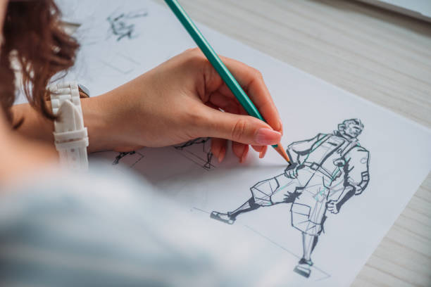 selective focus of illustrator drawing cartoon character on paper stock photo
