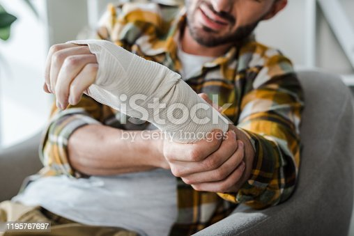 istock selective focus of injured arm of bearded man in bandage 1195767697