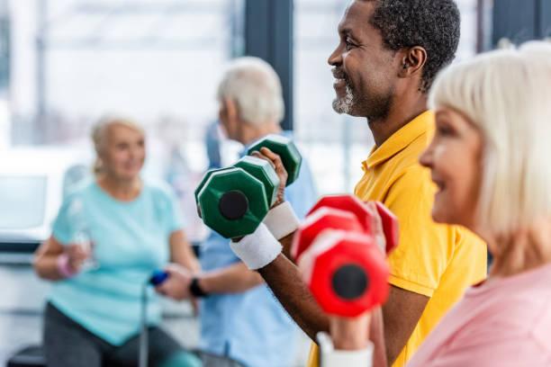 selektiv fokus för interracial mogna par gör övningen med hantlar på gymmet - active senior bildbanksfoton och bilder