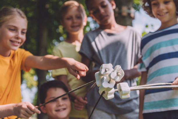selektiver Fokus des Kindes, das mit dem Finger auf süße Marshmallows in Stöcken in der Nähe von multikulturellen Jungen zeigt – Foto