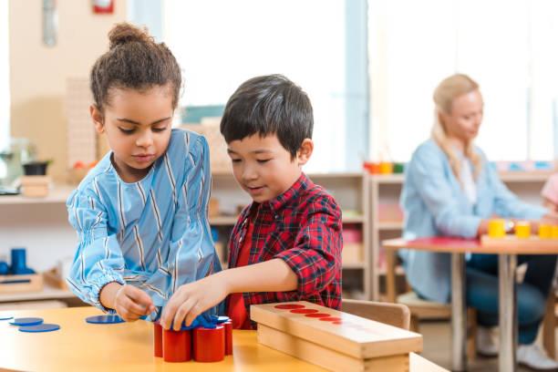 selectieve nadruk van jonge geitjes die onderwijsspel met leraar bij achtergrond in montessoriklasse vouwen - peuterschool stockfoto's en -beelden