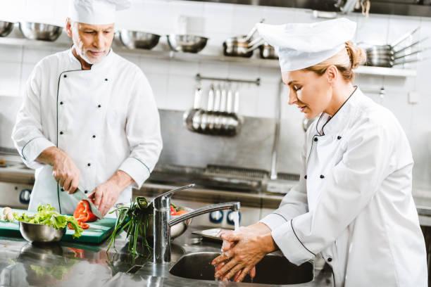 Selektiver Fokus der Köchinnen und Köche in doppelbäuerlichen Jacken, die in der Restaurantküche kochen – Foto