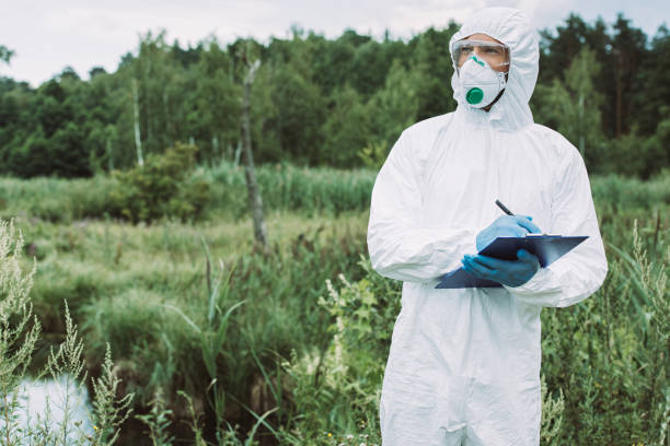 selective focus of male scientist in protective mask and suit writing in clipboard near water outdoors stock photo