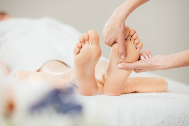 selective focus of masseur doing foot massage to adult woman in spa selective focus of masseur doing foot massage to adult woman in spa foot massage stock pictures, royalty-free photos & images