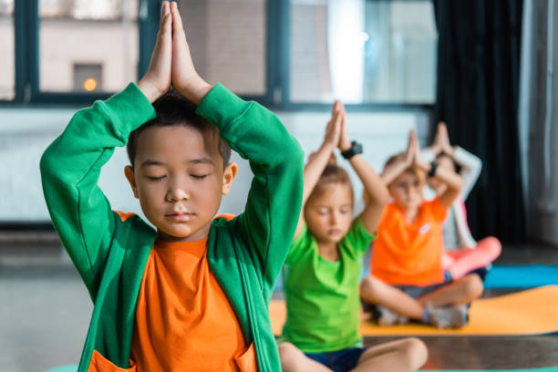 Selective focus of multicultural children meditating with clenched hands over heads in gym stock photo