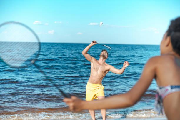 mise au point sélective de couple multiculturel, jouer au badminton sur la plage de sable fin - Photo
