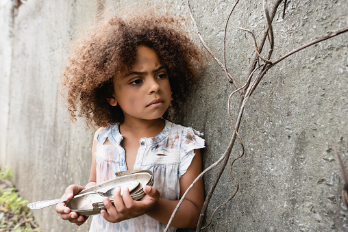 Selective focus of poor african american kid holding dirty metal plate and spoon near concrete wall on urban street
