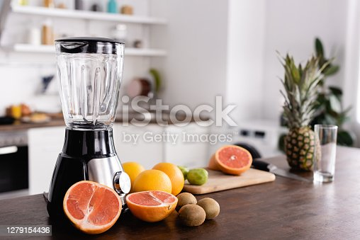 Selective focus of ripe fruits near blender on kitchen table