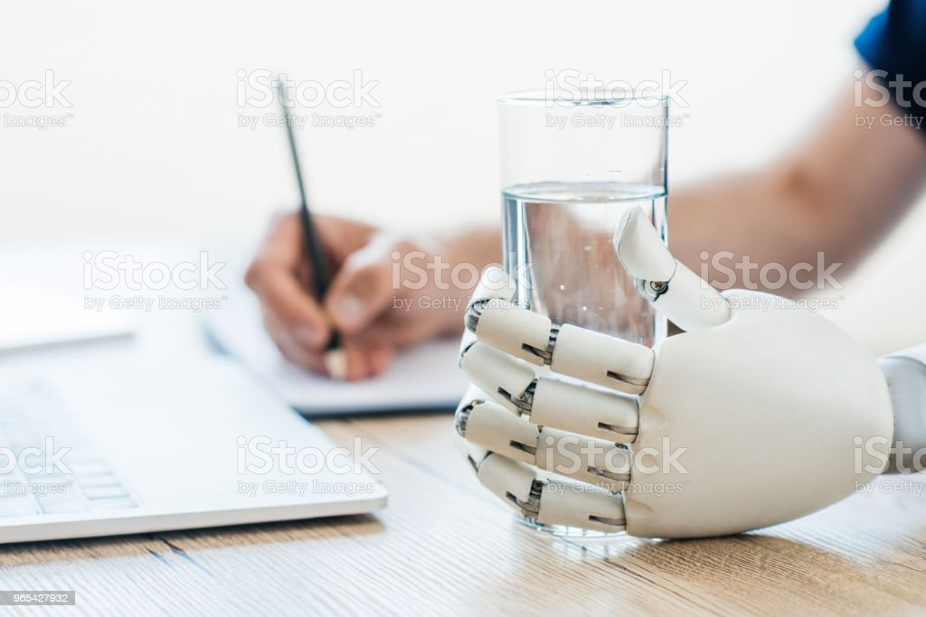 selective focus of robotic arm holding glass of water and person taking notes at wooden table zbiór zdjęć royalty-free