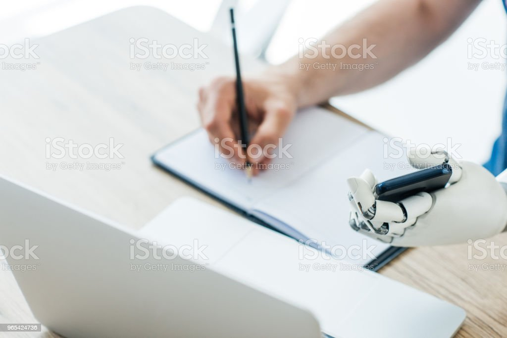 selective focus of robotic arm holding smartphone and human hand taking notes at workplace royalty-free stock photo