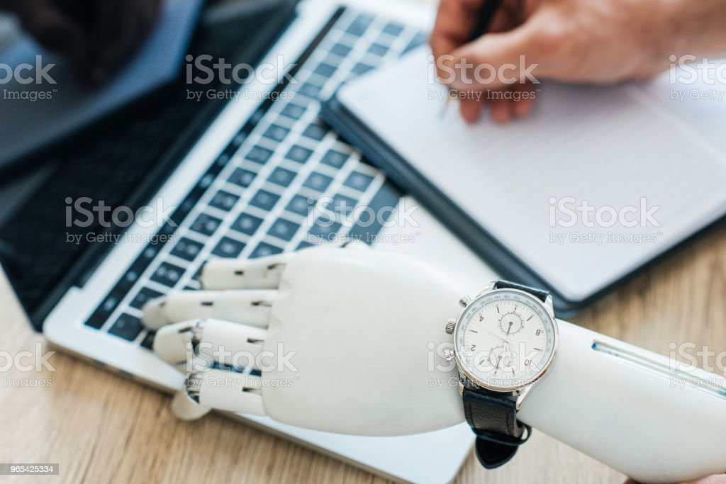 selective focus of robotic arm with wristwatch using laptop and human hand taking notes at wooden table royalty-free stock photo