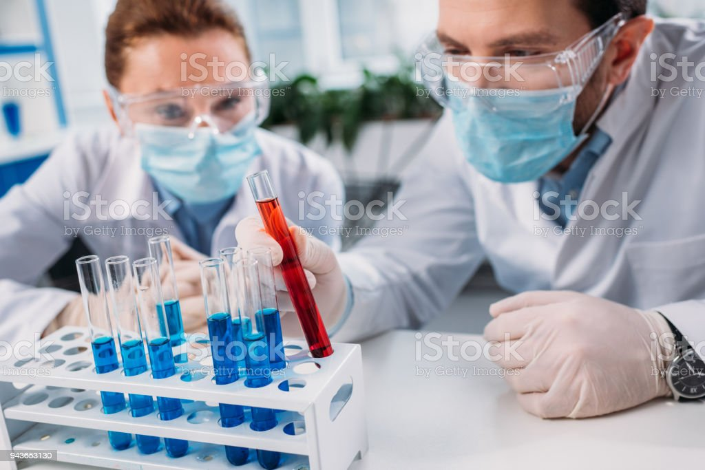 selective focus of scientific researchers in goggles and medical masks looking at reagents in tubes in lab stock photo