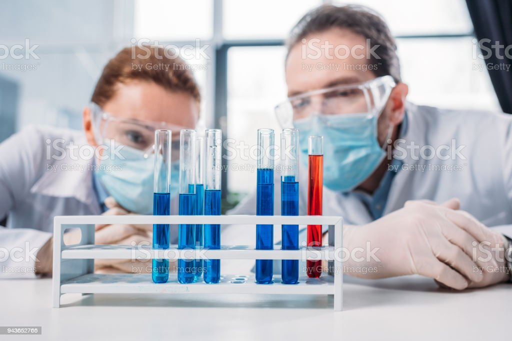 selective focus of scientific researchers in googles and medical masks looking at reagents in tubes in lab stock photo