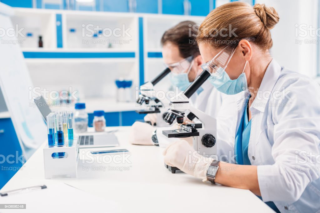 selective focus of scientists in medical masks and goggles looking through microscopes on regents in lab stock photo