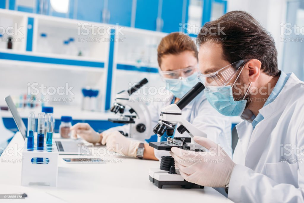 selective focus of scientists in medical masks working in lab together stock photo