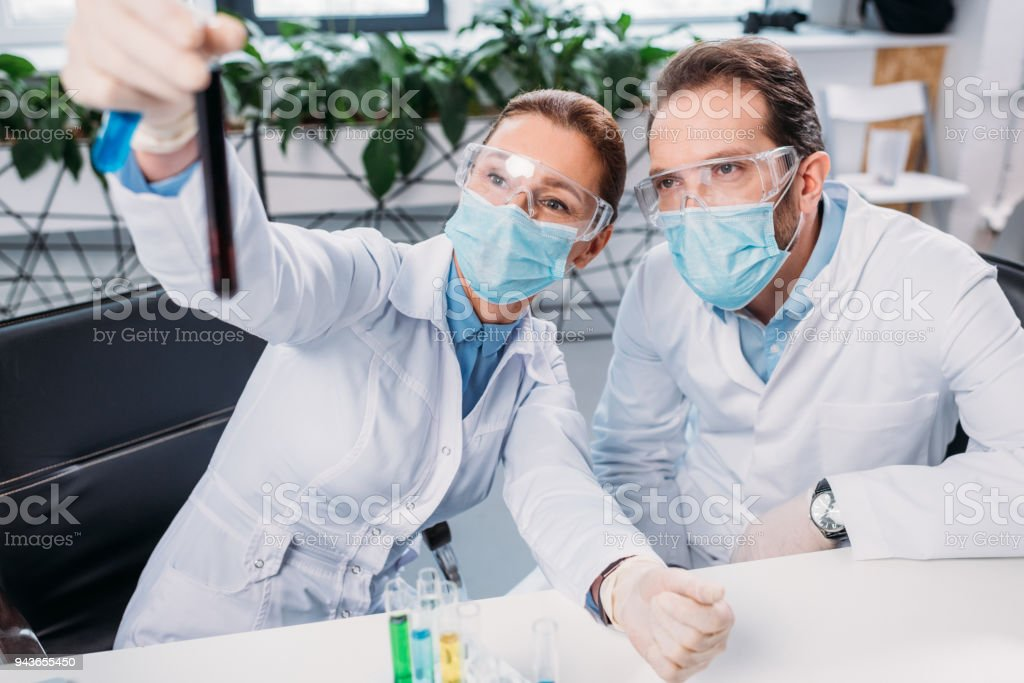 selective focus of scientists looking at reagent in laboratory stock photo