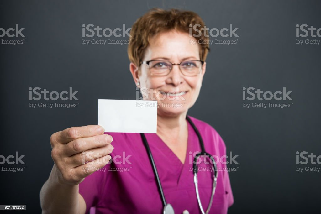Selective focus of senior lady doctor showing business card stock selective focus of senior lady doctor showing business card royalty free stock photo reheart Image collections
