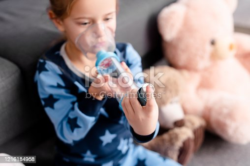 selective focus of sick kid using inhaler with spacer near soft toys